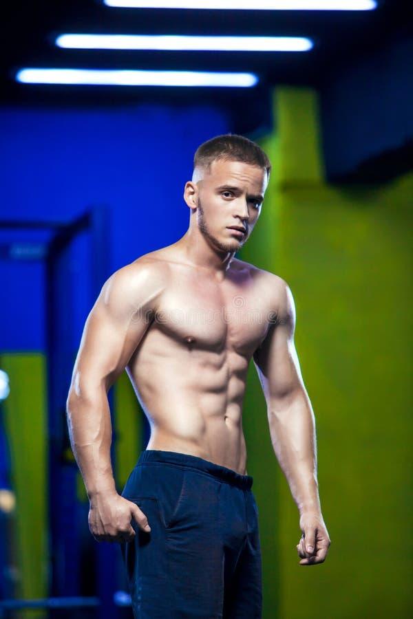 Portret van het sterke gezonde knappe Atletische Mensengeschiktheid Model stellen in de gymnastiek stock fotografie