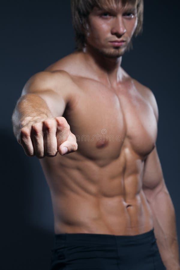 Portret van het sterke gezonde knappe Atletische Mensengeschiktheid Model stellen dichtbij donkergrijze muur stock foto's