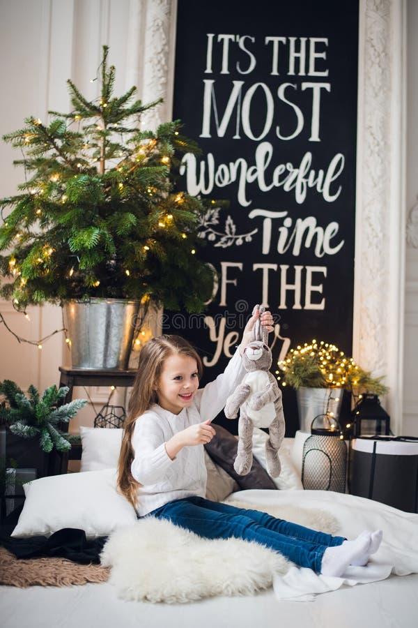 Portret van het stuk speelgoed van de meisjeholding konijntje Leuk meisje met snoezige stuk speelgoed zitting op een vloer thuis royalty-vrije stock afbeeldingen