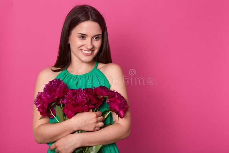 Portret van het tedere positieve jonge meisje opzij kijken, houdend dichte bos die van bloemen, van boeket van donkere roze pioen stock foto's