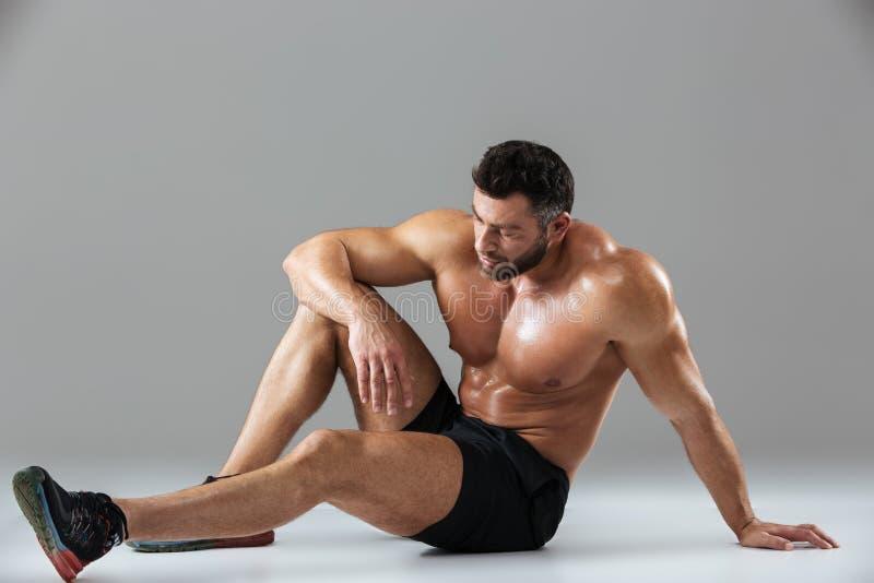 Portret van het vermoeide sterke shirtless mannelijke bodybuilder ontspannen stock fotografie