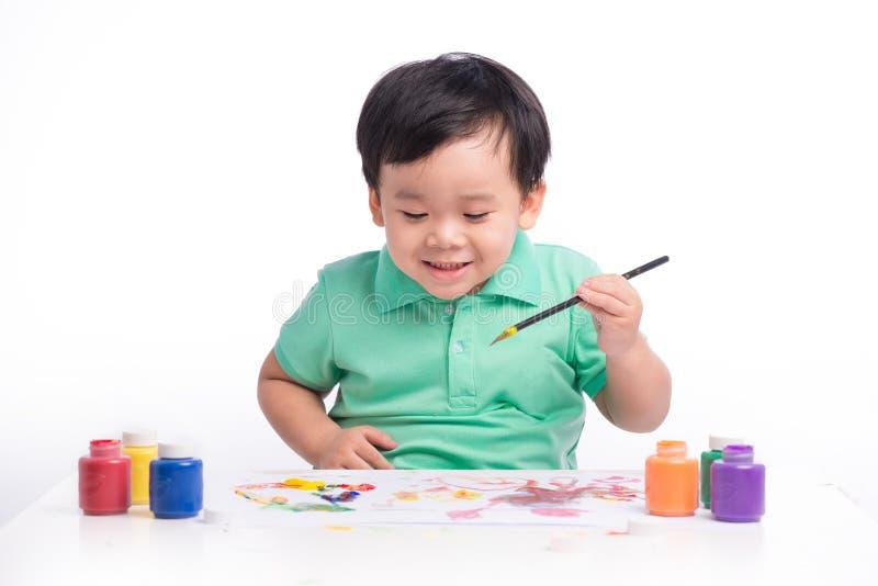 Portret van het vrolijke Aziatische jongen schilderen gebruikend waterverf stock afbeelding