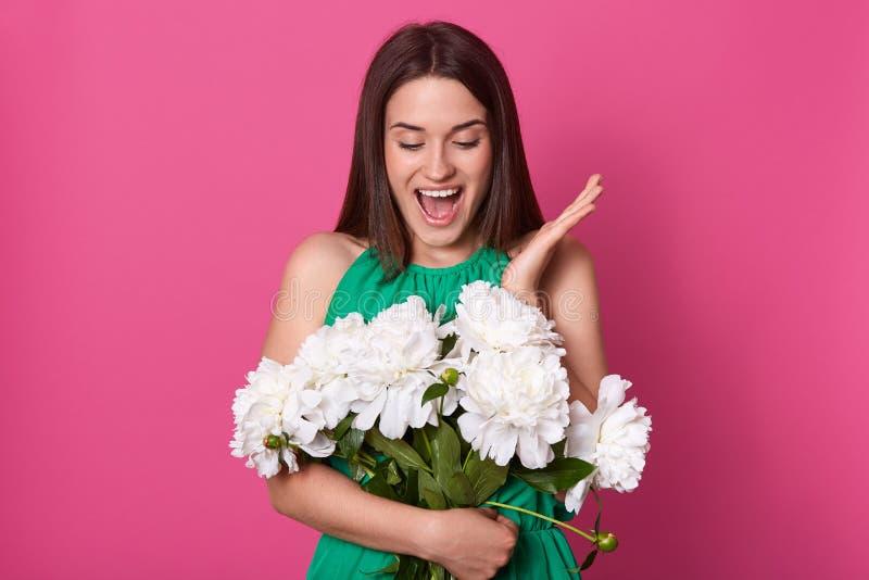 Portret van het vrolijke gelukkige jonge boeket van de vrouwenholding van witte pioenen, bekijkend hen met verrassing, die één ha stock foto