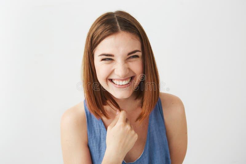 Portret van het vrolijke gelukkige jonge mooie meisje lachen die over witte achtergrond glimlachen royalty-vrije stock afbeelding