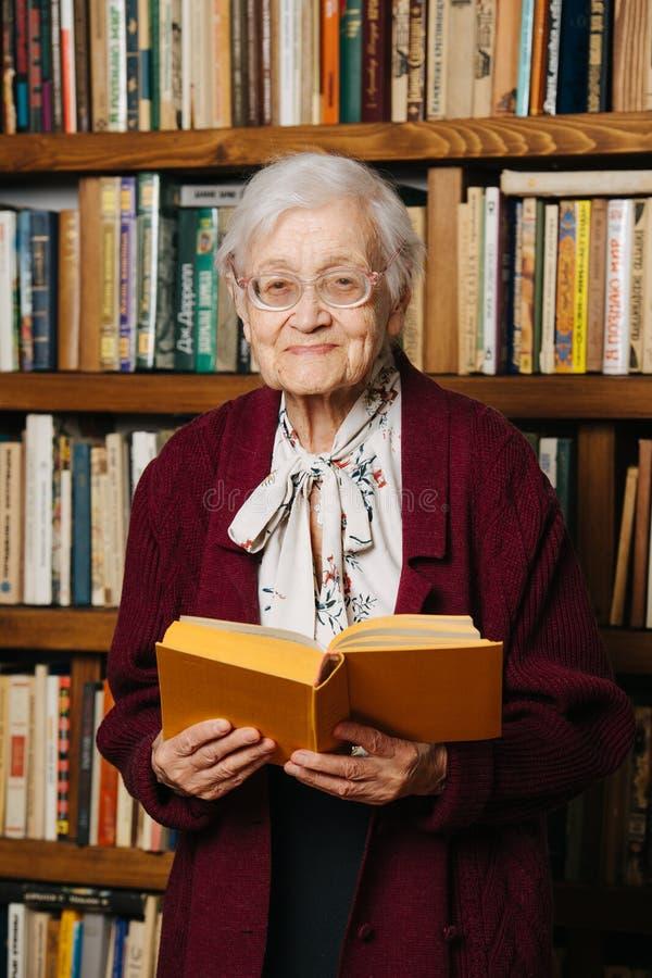 Portret van het vrolijke grijze haired boek van de vrouwenlezing dichtbij boekenrek thuis royalty-vrije stock fotografie