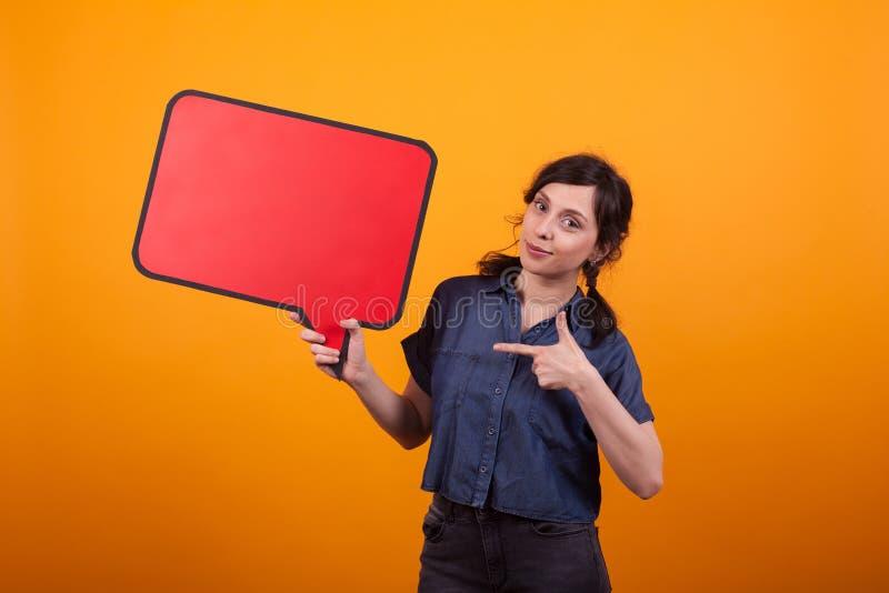 Portret van het vrolijke jonge vrouw richten op virtuele dialoog in studio over gele achtergrond royalty-vrije stock foto's