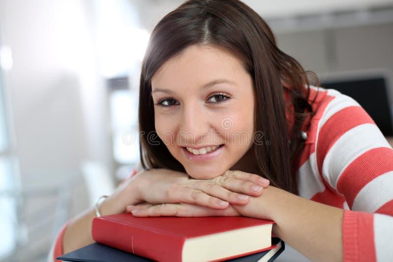 Portret van het vrolijke meisje glimlachen die op boeken leunen royalty-vrije stock fotografie