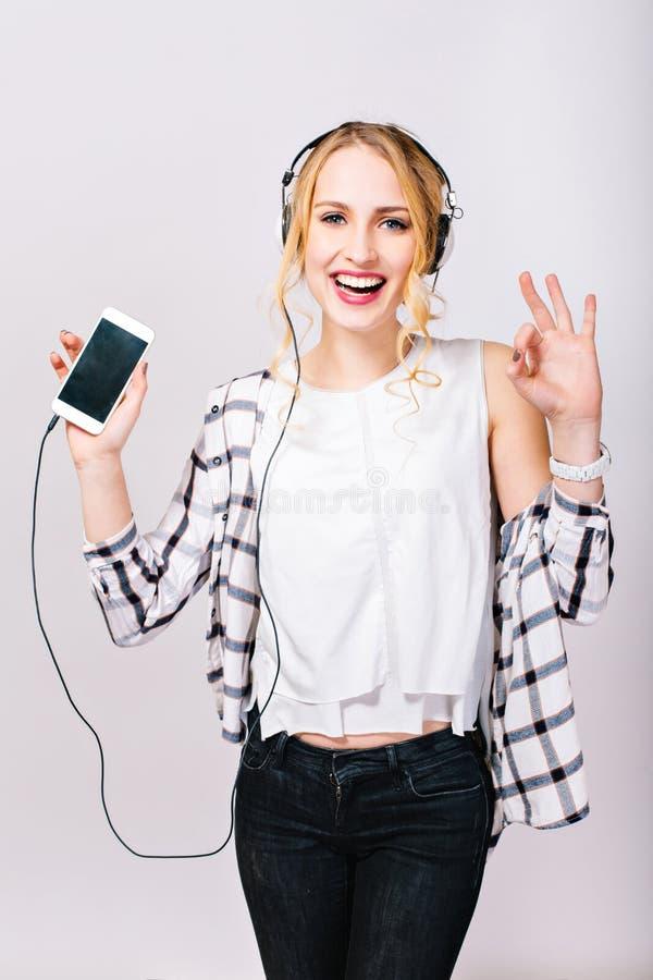 Portret van het vrolijke mooie blondemeisje luisteren aan muziek, het glimlachen en het bekijken camera Leasuretijd van vrij stock foto's