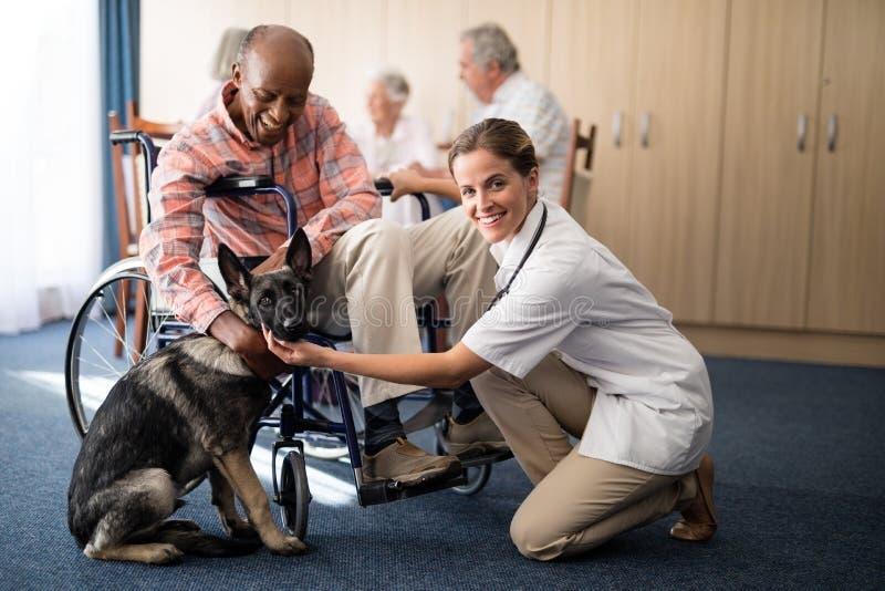 Portret van het vrouwelijke arts knielen door gehandicapt hoger mens het strijken puppy stock foto's