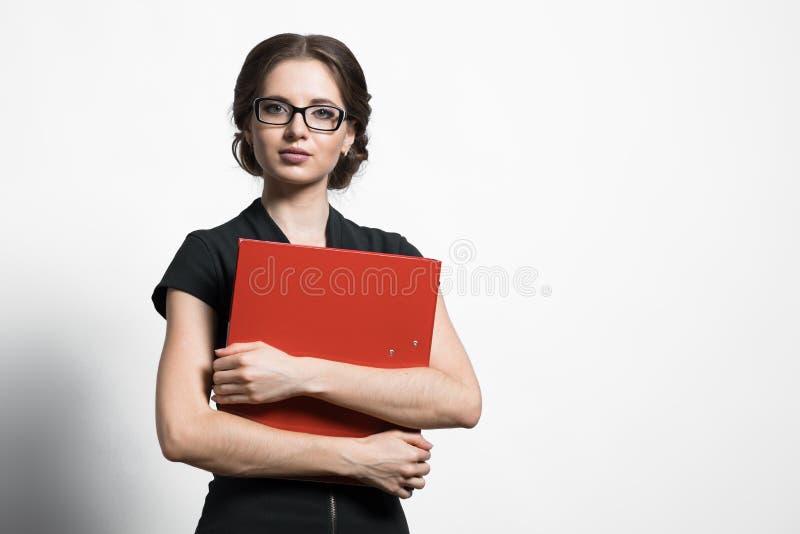 Portret van het zekere mooie jonge bindmiddel van de bedrijfsvrouwenholding in haar handen die zich op grijze achtergrond bevinde stock fotografie
