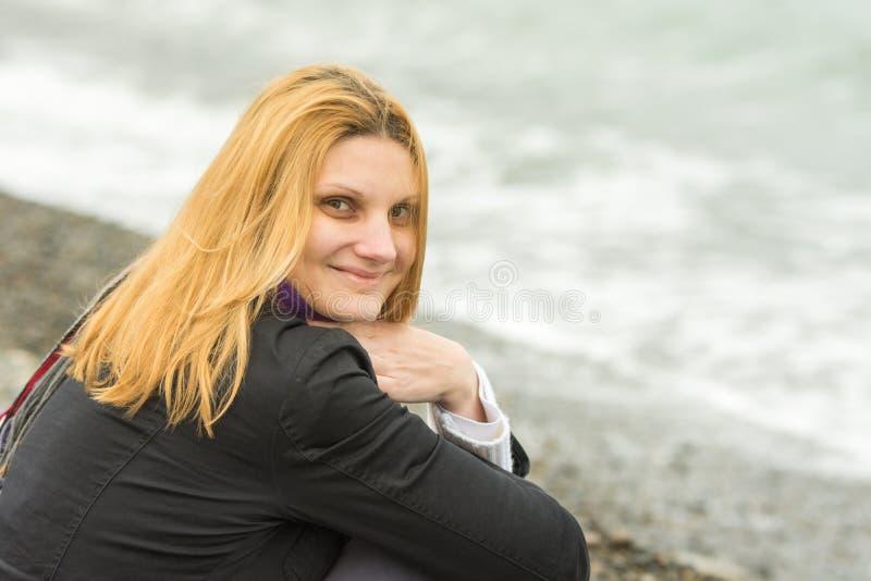 Portret van het zitten op strand die jonge vrouw in koud weer glimlachen royalty-vrije stock foto's