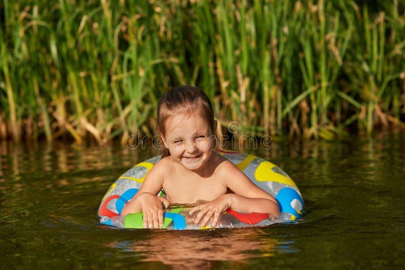 Portret van het zoete speelse kind zwemmen in rivier met speciaal materiaal, die het zwemmen gaan leren, hebbend prettige gezicht royalty-vrije stock fotografie
