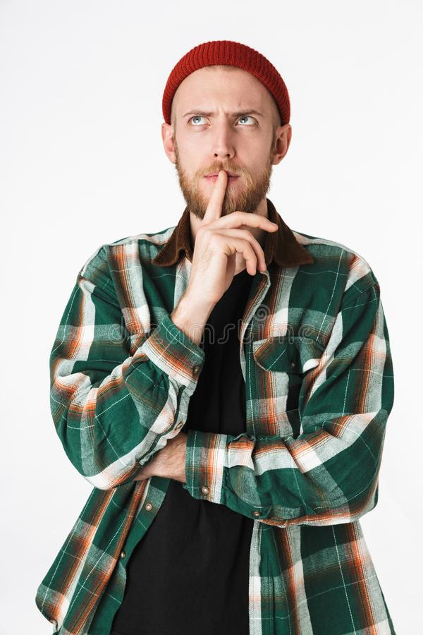 Portret van hipster gebaarde kerel die hoed en plaid de wijsvinger van de overhemdsholding op lippen dragen, terwijl status geïso royalty-vrije stock fotografie