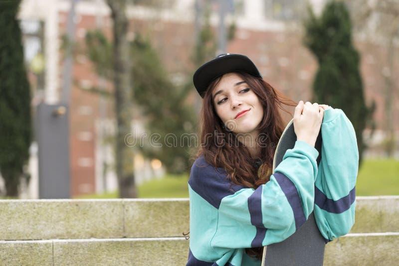Portret van hipster jonge vrouw met skateboard, stedelijke levensstijl stock afbeelding
