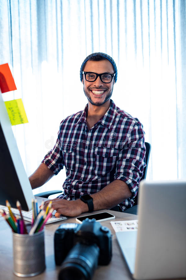 Portret van hipsterfotograaf het glimlachen bij camera terwijl het zitten bij bureau stock fotografie