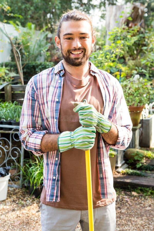 Portret van hipstertuinman met hulpmiddel bij tuin royalty-vrije stock afbeeldingen