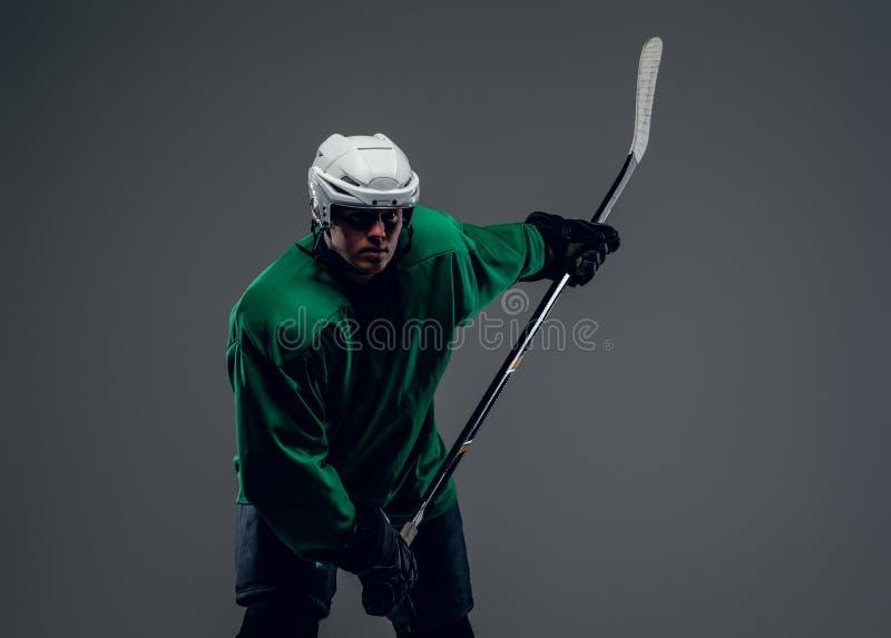 Portret van hockeyspeler op grijze achtergrond wordt geïsoleerd die royalty-vrije stock fotografie