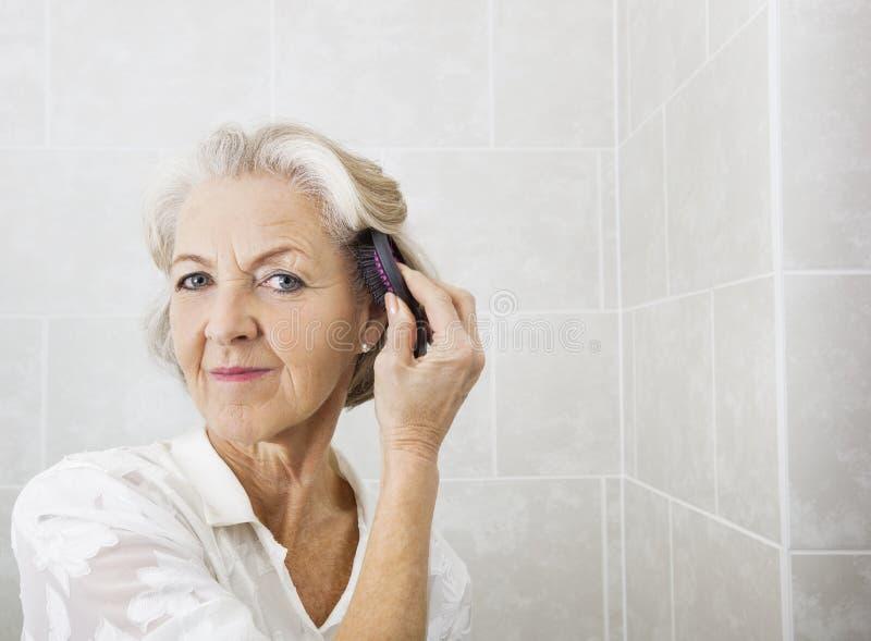Portret van hoger vrouw het borstelen haar in badkamers royalty-vrije stock fotografie