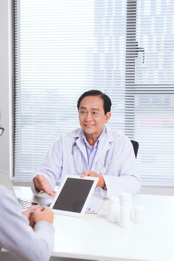 Portret van hogere artsenzitting bij zijn bureau in medisch bureau stock foto