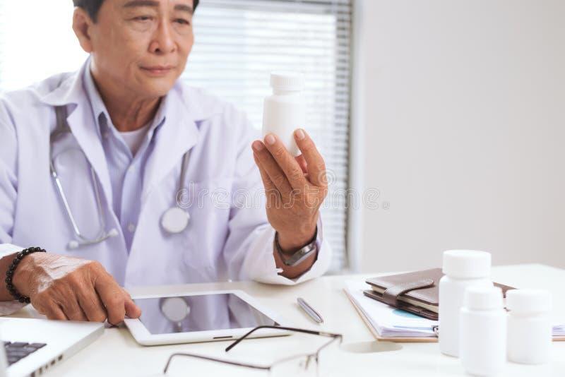 Portret van hogere artsenzitting bij zijn bureau in medisch bureau stock afbeeldingen