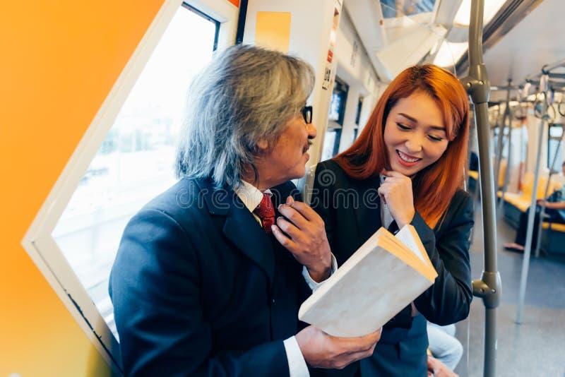 Portret van Hogere manager en jonge werknemer in formeel kostuum die een gesprek samen op trein hebben stock foto's