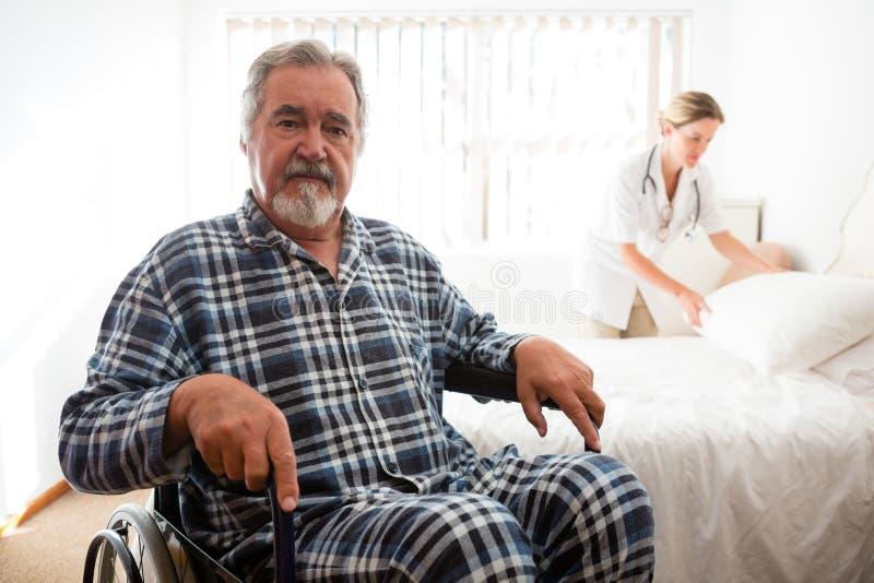 Portret van hogere mensenzitting op rolstoel terwijl arts het werken royalty-vrije stock fotografie