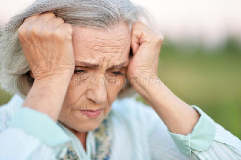 Portret van hogere mooie vrouw met hoofdpijn stock foto