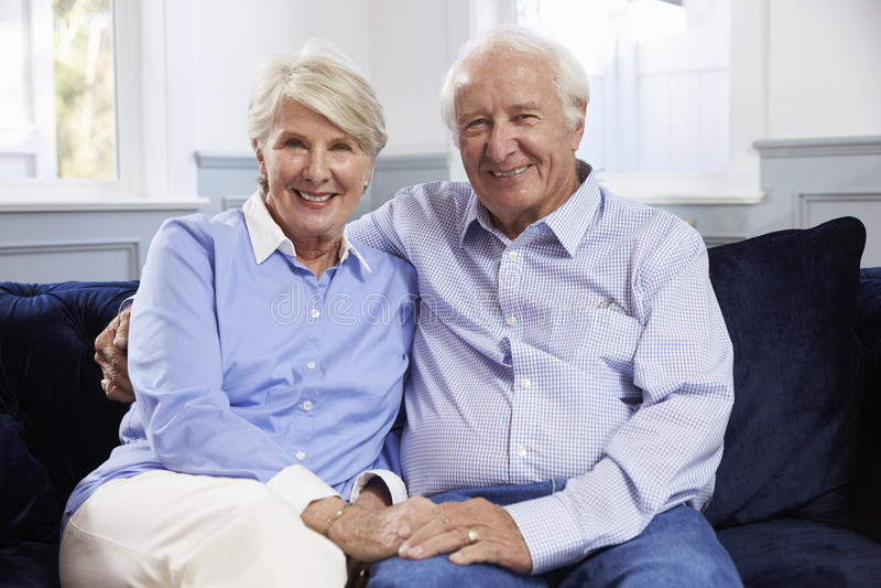 Portret van hogere paarzitting op bank thuis royalty-vrije stock foto's