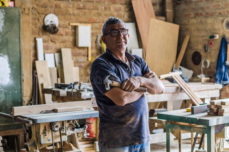 Portret van hogere timmerman in zijn workshop en het bekijken camera stock afbeelding