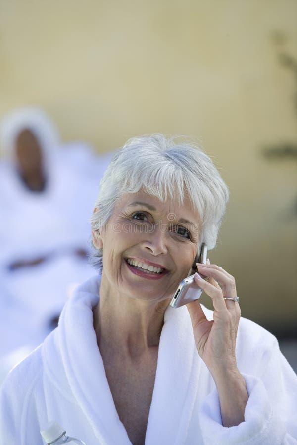 Portret van Hogere Vrouw in Badjas die Cellphone gebruiken stock foto