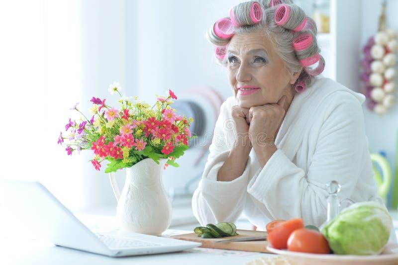 Portret van hogere vrouw in badjas met krulspelden die bij lijst met laptop zitten royalty-vrije stock foto