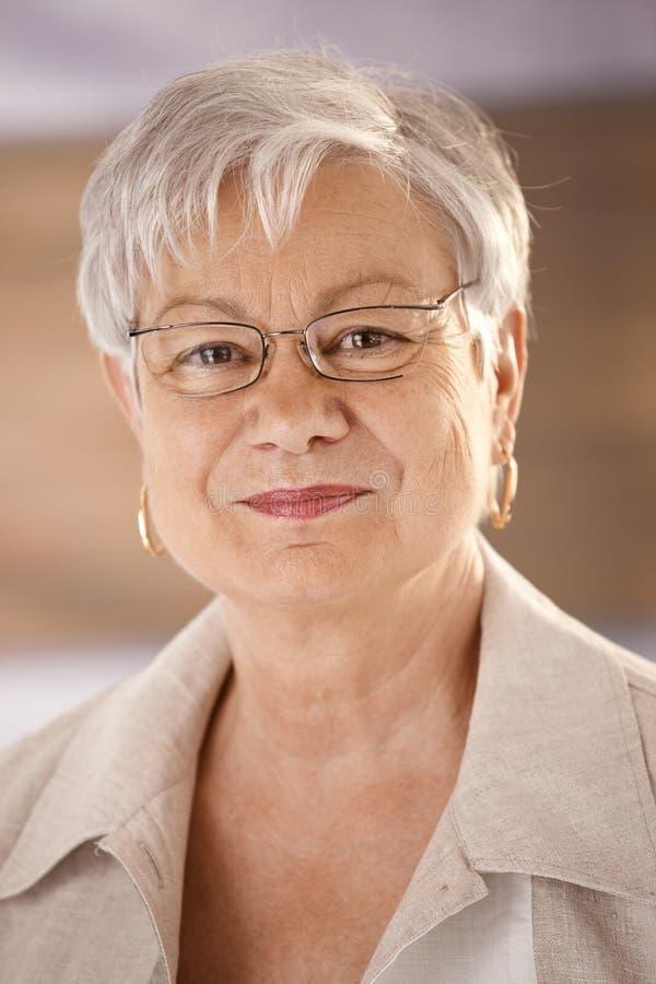 Portret van hogere vrouw die glazen dragen stock foto's