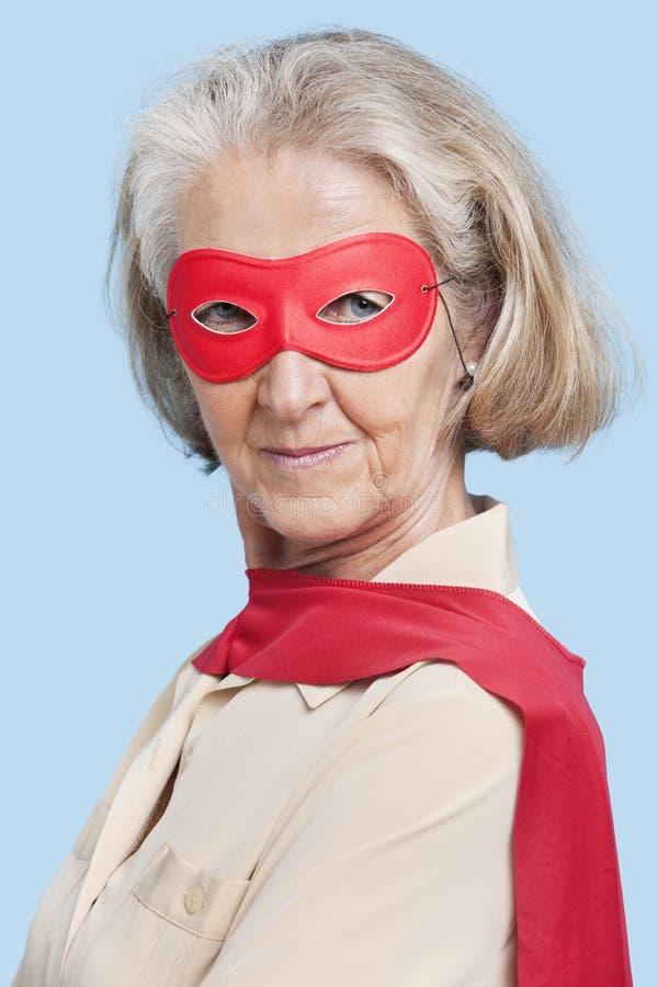 Portret van hogere vrouw die superherokostuum dragen tegen blauwe achtergrond royalty-vrije stock fotografie