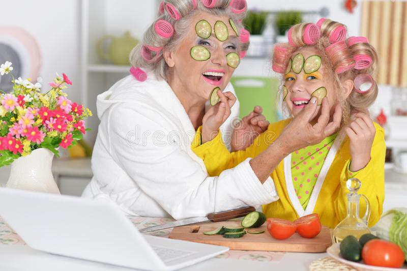Portret van hogere vrouw en kleindochter bij keuken stock foto's
