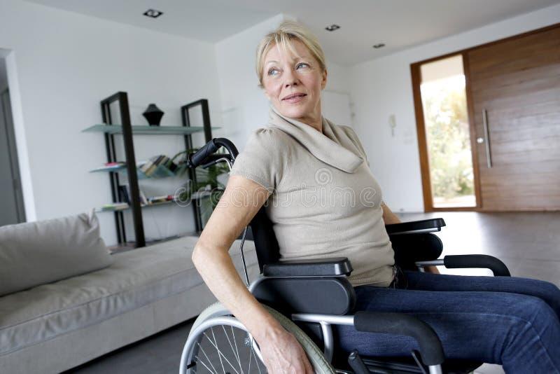 Portret van hogere vrouw in rolstoel thuis stock afbeelding