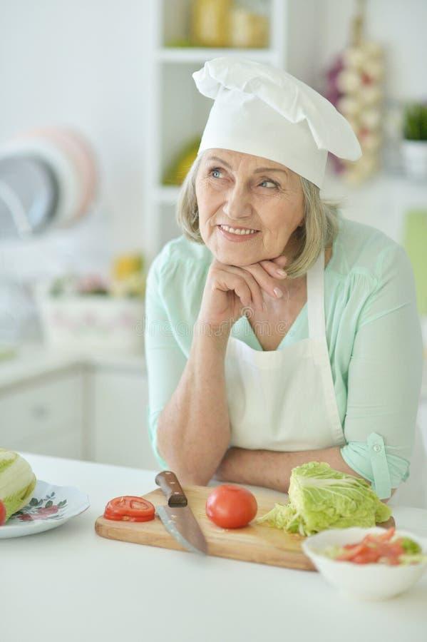 Portret van hogere vrouwenchef-kok bij keuken thuis royalty-vrije stock afbeeldingen