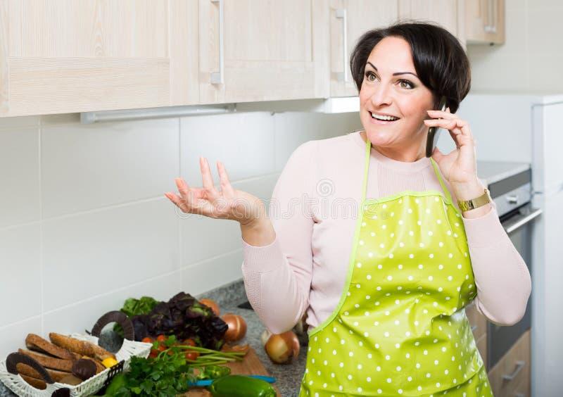 Portret van huisvrouw in schort die op telefoon spreken royalty-vrije stock fotografie