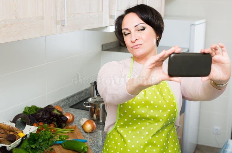 Portret van huisvrouw in schort die selfie in binnenlandse keuken maken royalty-vrije stock foto's