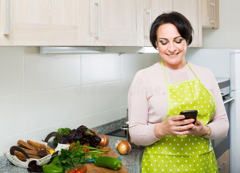 Portret van huisvrouw in schort die sms met recept ontvangen royalty-vrije stock foto