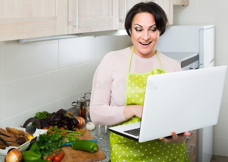 Portret van huisvrouw in schort met laptop bij keuken stock afbeelding