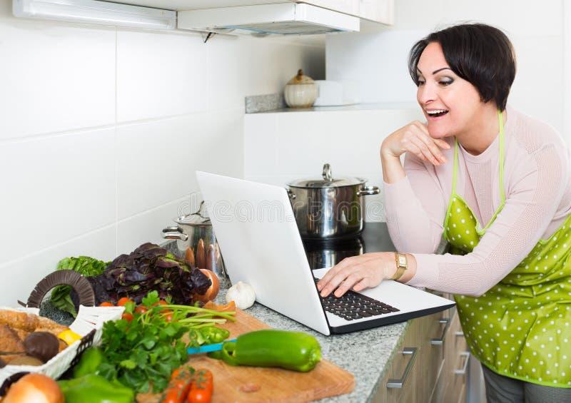 Portret van huisvrouw in schort met laptop bij keuken stock afbeeldingen