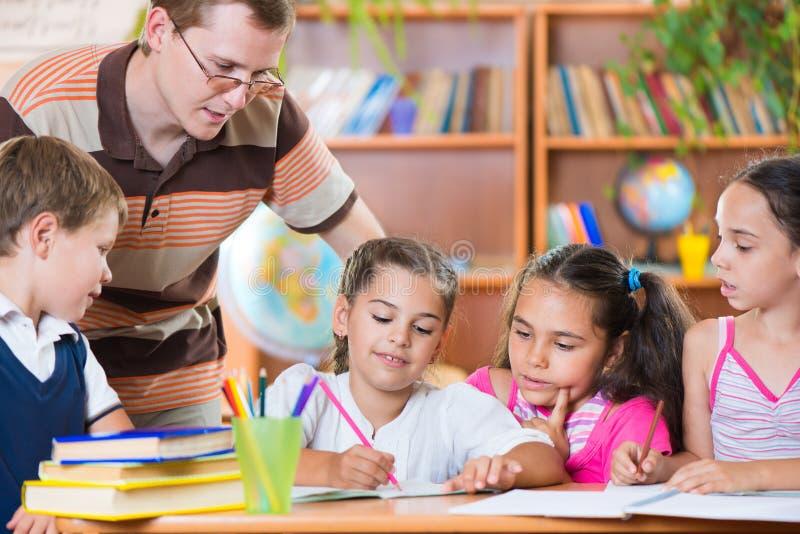 Portret van ijverige schoolkinderen en hun leraar stock afbeelding