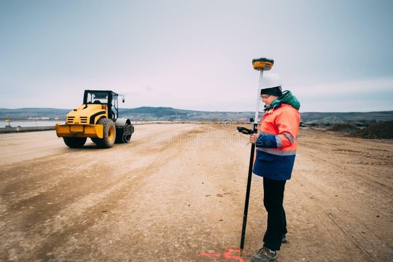 Portret van ingenieur op bouwwerf, landmeter die gps systeem en theodoliet op wegbouwwerf gebruiken royalty-vrije stock fotografie