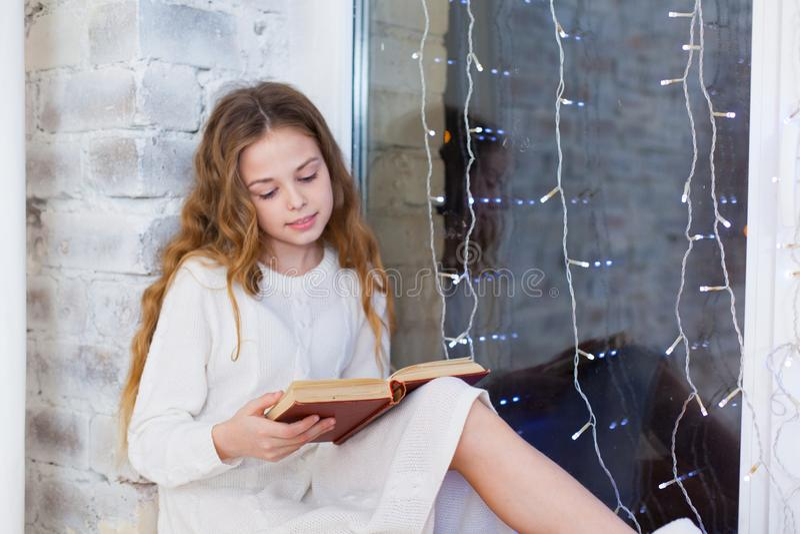 Portret van 10 jaar het oude van de kindlezing boek op het venster op Kerstmis stock foto