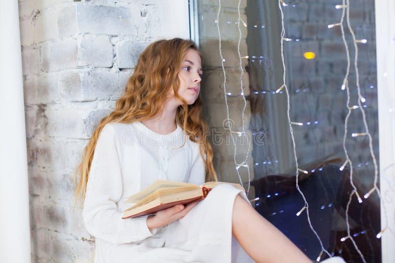 Portret van 10 jaar het oude van de kindlezing boek op het venster op Kerstmis stock fotografie