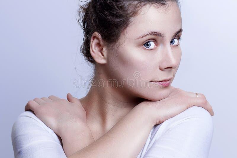 Portret van jong aantrekkelijk Kaukasisch meisje op grijze achtergrond Verzacht blik van mooie vrouw royalty-vrije stock foto