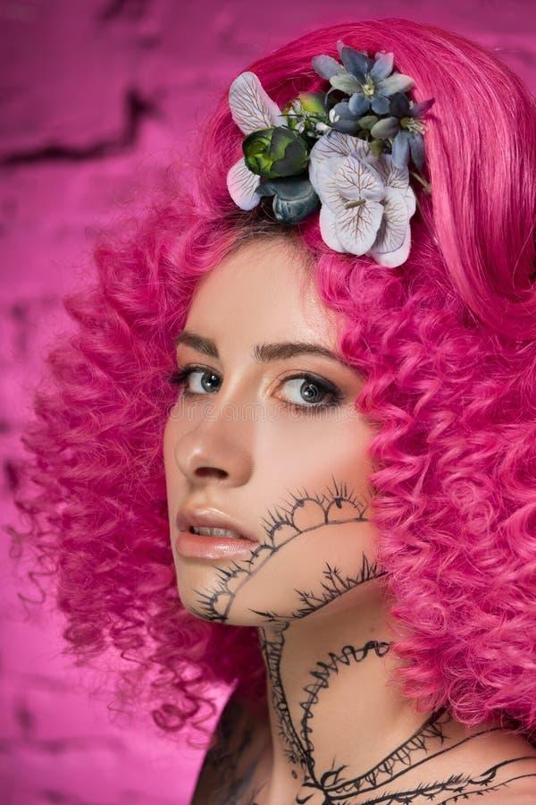 Portret van jong aantrekkelijk Kaukasisch meisjesmodel met het krullende heldere roze haar van de afrostijl, getatoeeerde die gez stock afbeeldingen