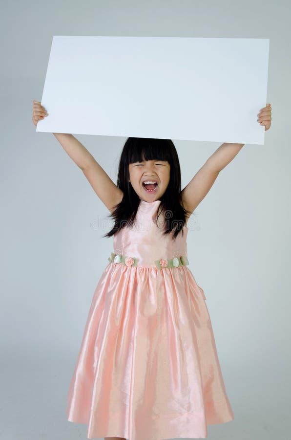 Portret van jong Aziatisch meisje die leeg aanplakbord houden royalty-vrije stock foto