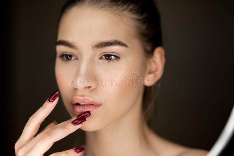 Portret van jong bruin-haired meisje die met natuurlijke make-up haar vingers op haar gezicht houden stock fotografie