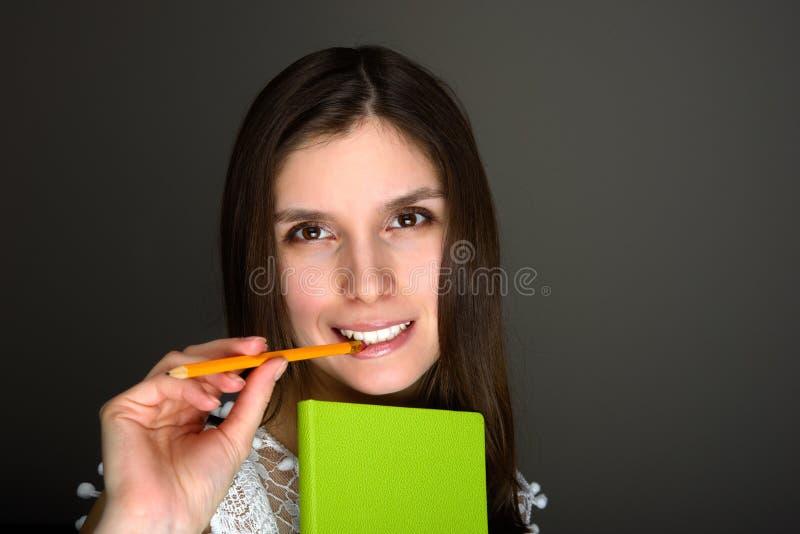 Portret van jong donkerbruin vrouwelijk chewning potlood stock fotografie